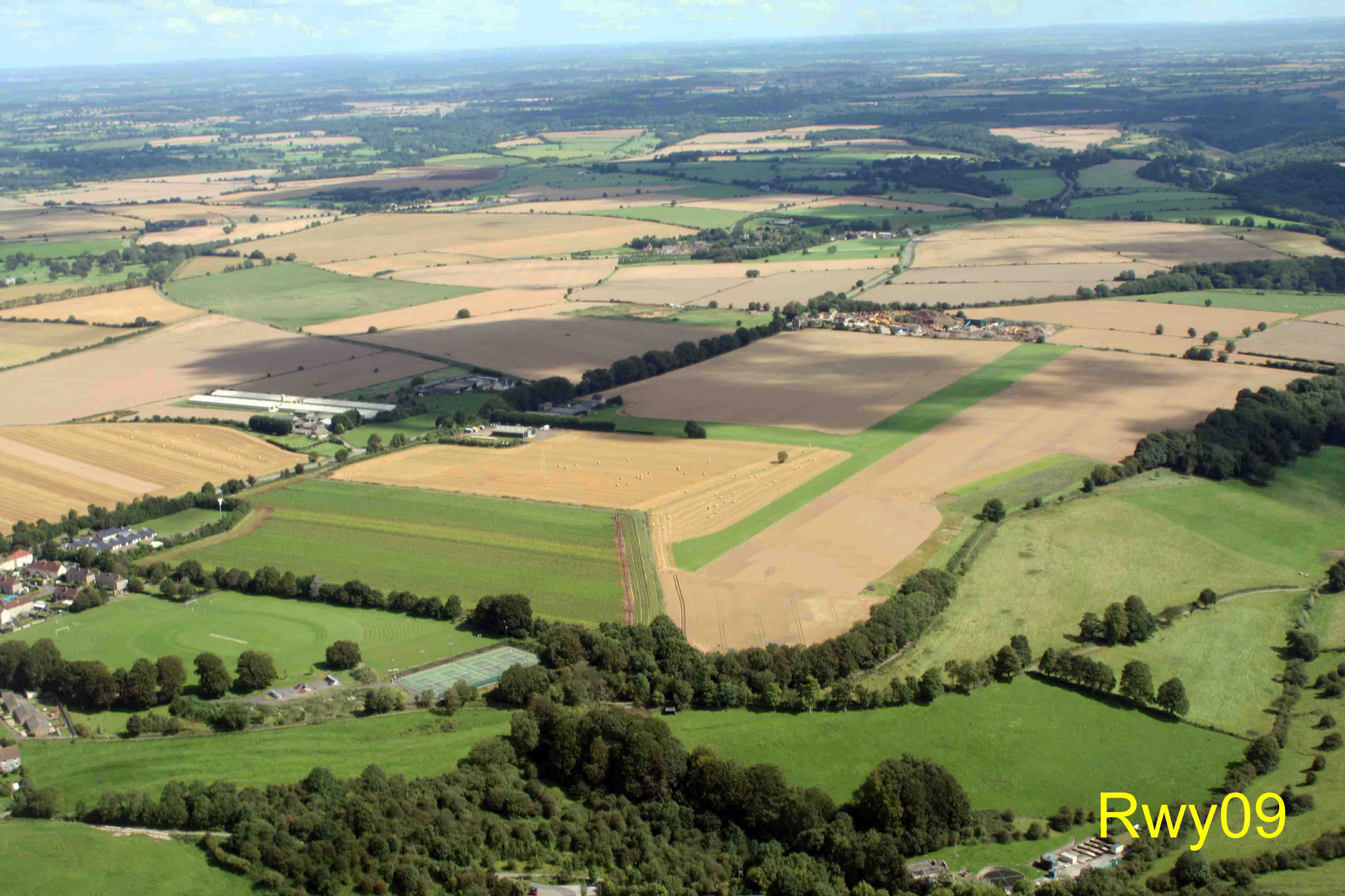 Garston Farm from the West. Rwy 09 approach through the gap between trees.  Marshfield village is bottom-left.